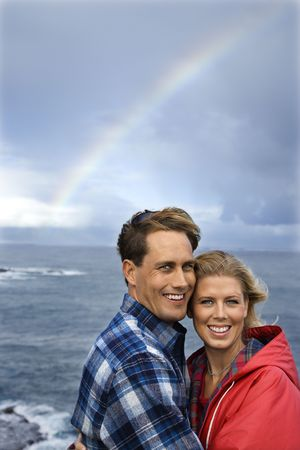 Caucasian mid-adult couple standing by ocean with rainbow in background in Maui, Hawaii. photo