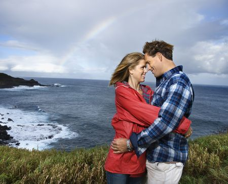 Caucasian mid-adult couple embracing by ocean with rainbow in background in Maui, Hawaii. photo