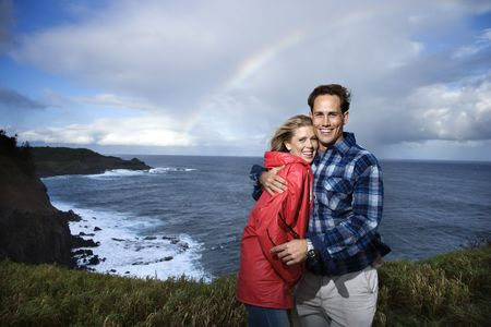 Caucasian mid-adult  couple embracing in front ocean with rainbow in background in Maui, Hawaii. photo