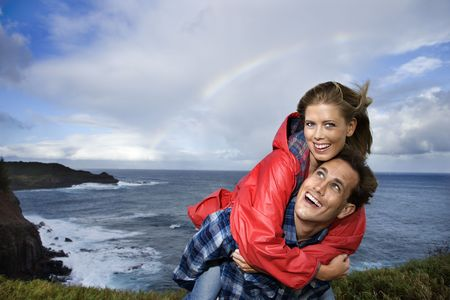 raincoat: Caucasian mid-adult couple piggybacking by ocean with rainbow in background in Maui, Hawaii.