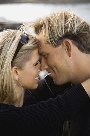 two people with others: Caucasian mid-adult couple embracing and gazing into each others eyes.