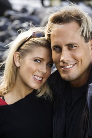 Portrait of Caucasian mid-adult couple holding each other and looking at viewer smiling. photo