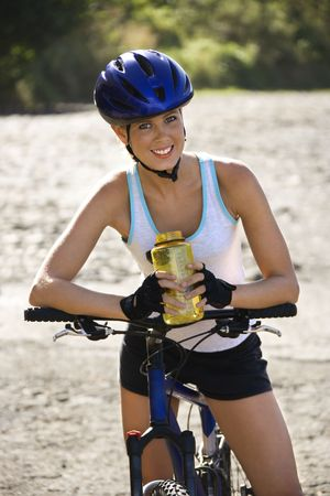 water bottle: Caucasian mid-adult woman wearing bicycle helmet, sitting on bycycle, holding water bottle, looking at viewer, smiling.