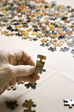 Close-up of Elderly Caucasian womans hand holding puzzle piece.