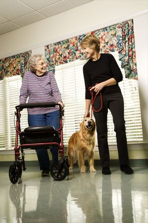 Elderly Caucasian woman using walker and middle-aged woman walking dog in hallway of retirement community center.