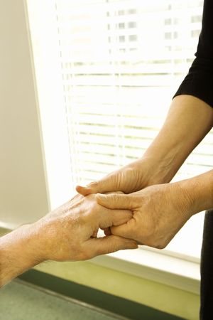 Woman holding mature womans hand.