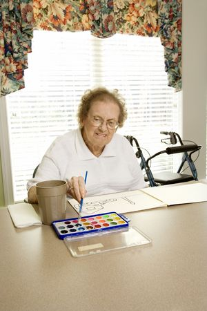 Elderly Caucasian woman painting with watercolors at retirement community center. photo