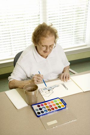 Elderly Caucasian woman painting with watercolors at retirement community center. Stock Photo