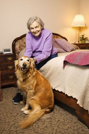 Elderly Caucasian woman and dog in her bedroom at retirement community center. photo