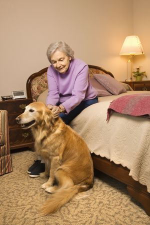 Elderly Caucasian woman and dog in bedroom at retirement community center. photo