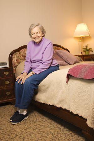Elderly woman in her bedroom at retirement community center. photo