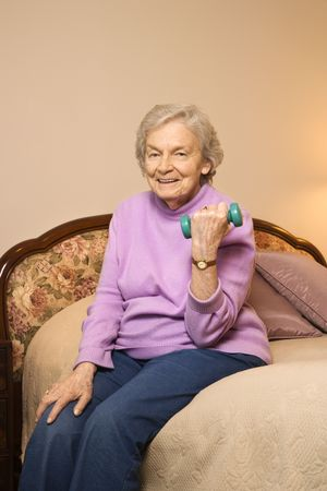 strengthen: Elderly Caucasian  woman in her bedroom at retirement community center lifting weights to strengthen arms.