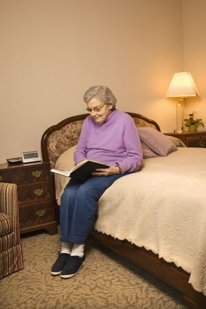 Elderly Caucasian woman in  bedroom at retirement community center reading a book. photo