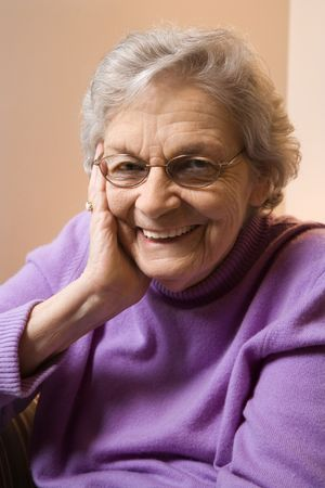 Elderly Caucasian woman smiling with hand on face. Stock Photo