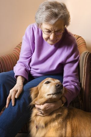 Elderly Caucasian woman in bedroom at retirement community center petting therapy dog. photo