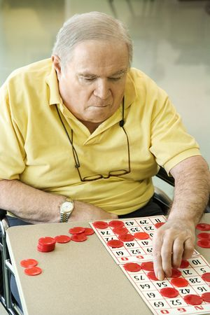 Elderly Caucasian man sitting in wheelchair playing game at retirement community center.