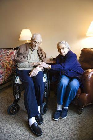 Elderly Caucasian couple in bedroom at retirement community center. photo
