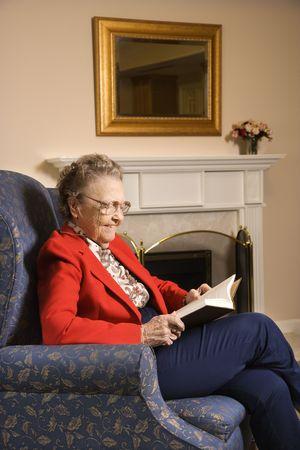 mujer leyendo libro: Ancianos mujer de raza cauc�sica libro de lectura en silla de jubilaci�n en centro comunitario.  Foto de archivo