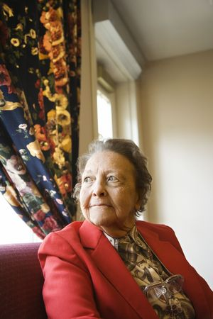 Elderly Caucasian  woman by window at retirement community center. photo