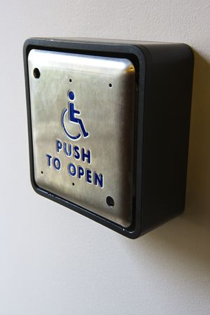 physically: Metal door entrance button for physically challenged or handicapped people.