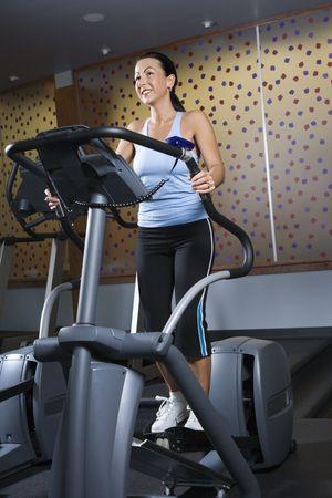 eliptica: Hembra cauc�sica del adulto primero en la m�quina el�ptica en el gym.