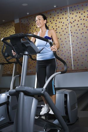 prime adult: Prime adult Caucasian female on elliptical machine at gym.