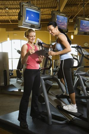 elliptical: Prime adult Caucasian female on elliptical machine at gym with trainer.