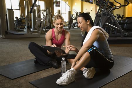 personal trainer: Prime adult Caucasian female with personal trainer at gym.