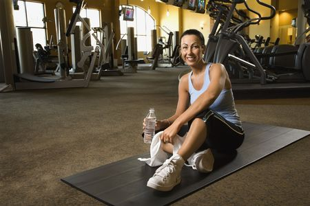 prime adult: Prime adult Caucasian female sitting on mat on gym floor.