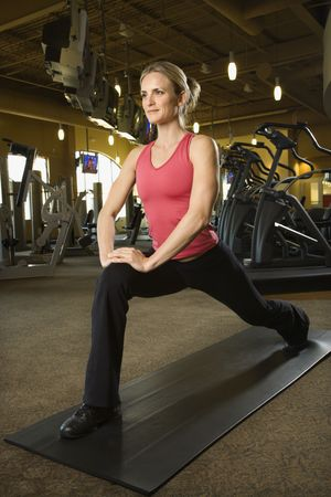 Prime adult Caucasian female stretching on mat in gym. Stock Photo - 1799023