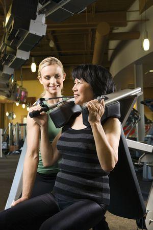 prime adult: Prime adult Caucasian female trainer helping Asian mature adult female on exercise machine.
