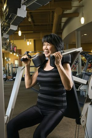 Mature Asian adult female using exercise machine at gym.