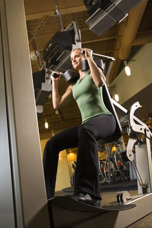 prime adult: Prime adult Caucasian female using exercise equipment at gym.