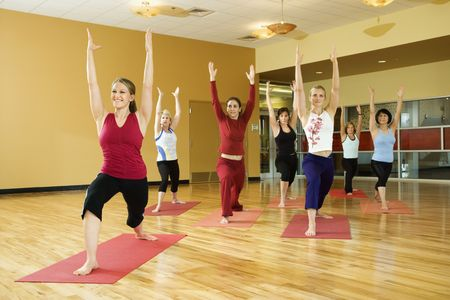 instruct: Prime adult female Caucasians in yoga class.