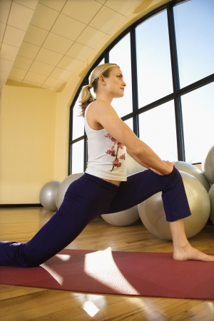 prime adult: Caucasian prime adult female stretching at gym.