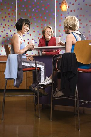health club: Mature Asian and Caucasian adult females sitting at table in health club cafeteria.