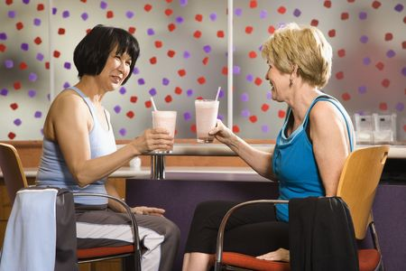 Mature Asian and Caucasian adult females sitting at table in health club cafeteria. photo