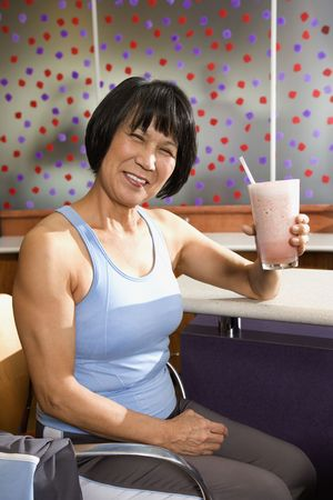 health club: Mature Asian adult female sitting at table in health club cafeteria.