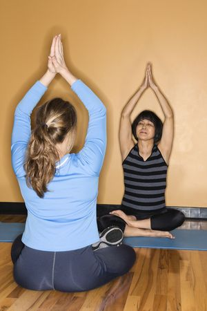 prime adult: Mature Asian adult female doing yoga with prime adult Caucasian female at gym. Stock Photo