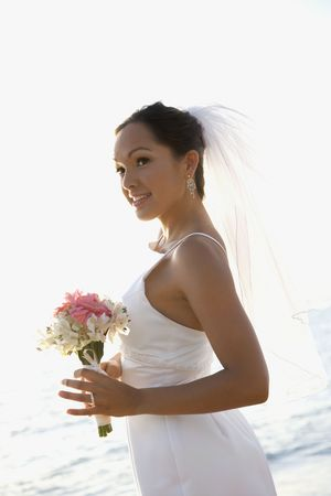 Young adult female Caucasian bride holding bouquet on beach. Stock Photo - 1795506