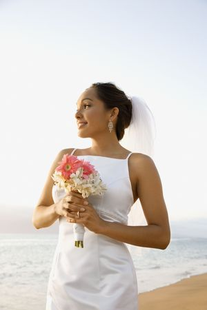 Young adult female Caucasian bride holding bouquet on beach. photo