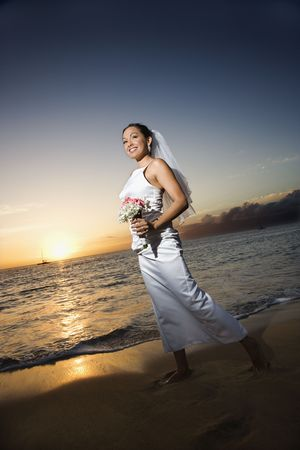Young adult female Caucasian bride walking holding bouquet on beach. photo