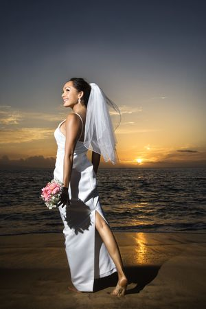 Young adult female Caucasian bride standing holding bouquet on beach.