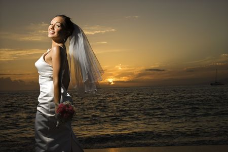 Young adult female Caucasian bride on beach. photo