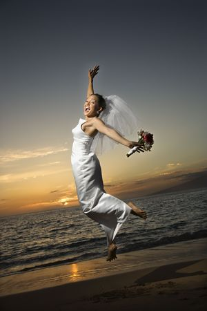 Young adult female Caucasian bride jumping on beach. photo