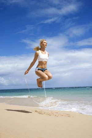 Caucasian young adult woman jumping rope on beach. Stock Photo