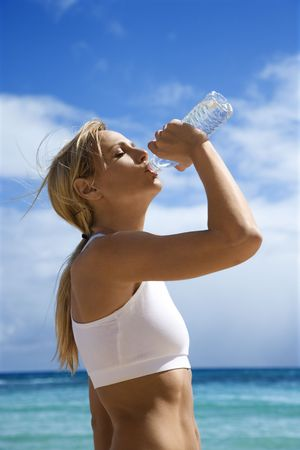Caucasian young adult woman drinking water on beach. photo