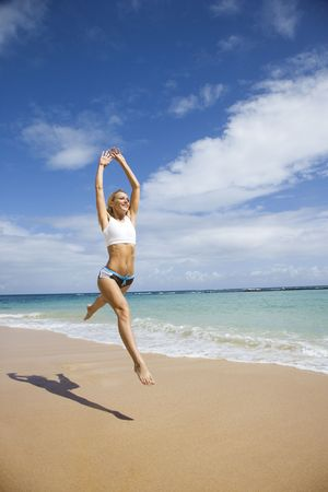 Caucasian young adult woman jumping on beach.