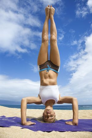 headstand: Caucasian young adult woman doing yoga on beach.