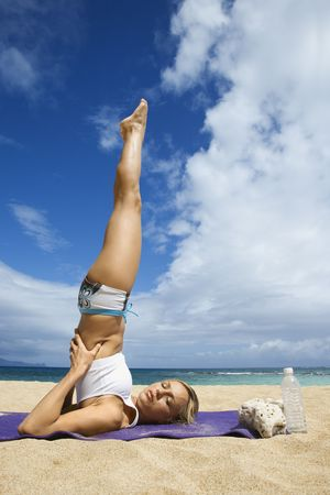 Caucasian young adult woman doing yoga on beach. Stock Photo - 1795586